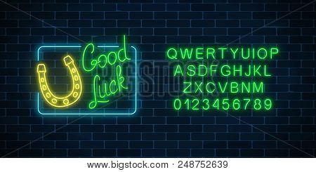Glowing neon sign with good luck wish and horseshoe in rectangle frame with alphabet on dark brick wall background. Hand drawn lettering and horse shoe for luck. Vector illustration. stock photo