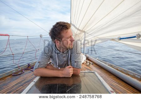 young european man sitting on yacht looking at sea. Travelling on old boat with sail. Concept of free lifestyle stock photo