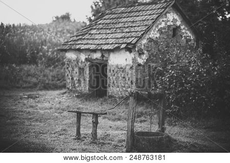 Abandoned house. House barrack with old well in yard. Rural lifestyle, countryside. Decay, decline, ruins. Architecture, structure, construction Village with abandoned building vintage filter stock photo