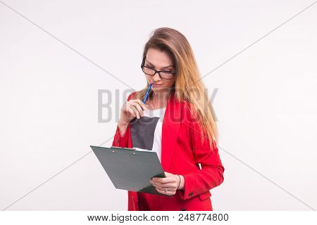 Portrait of young business woman in red jacket wih paper clip in hands stock photo
