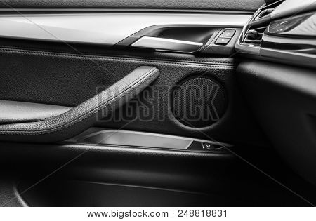 Door handle with Power window control buttons of a luxury passenger car. Black leather interior of the luxury modern car. Modern car interior details. Car detailing. Black and white stock photo