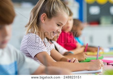 Smiling scholar girl sitting with other children in classroom and writing on textbook. Happy student