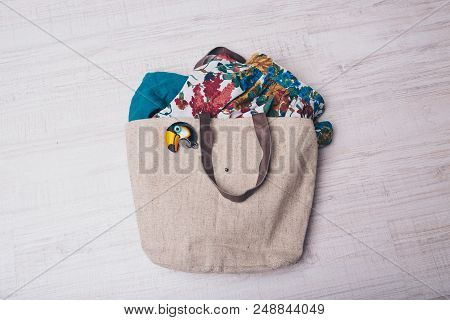 fabric bag filled with clothes and fabrics with bird icon on white background stock photo