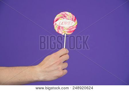 Sweet feelings. Lollipop with word love. Male hand holds lollipop with inscription love. Romantic gift for her. Gift for romantic holiday valentines day. Share his romantic feelings offers lollipop. stock photo