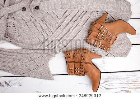 Flat lay close up brown heel boots and woolen coat. Brigh wooden background. stock photo