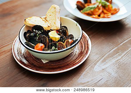Appetizing dish. Selective focus of appetizing seafood dish with some nice mussels with tomatoes and lemon in creamy sauce stock photo