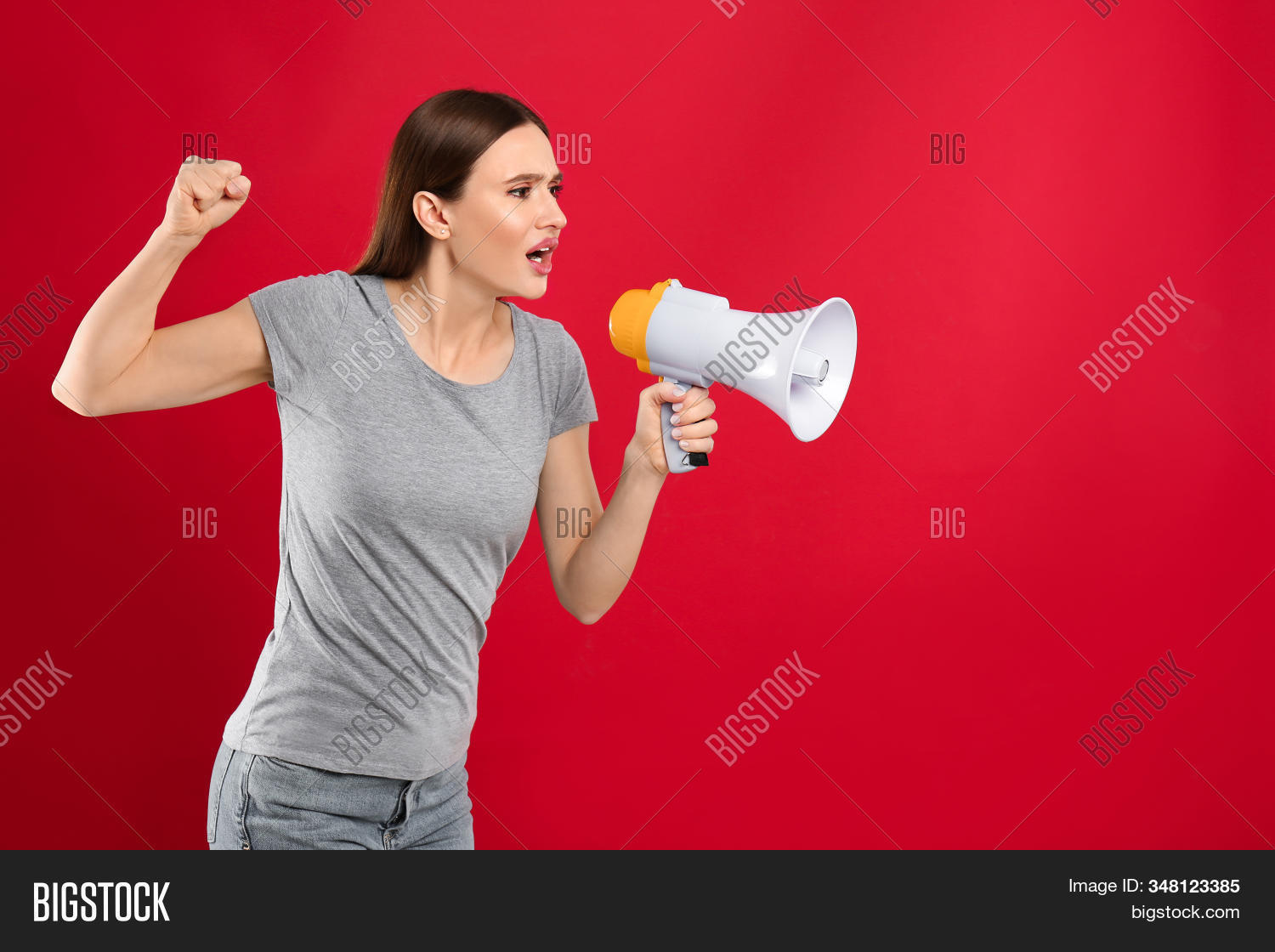 Young woman with megaphone on red background