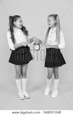 Keep your students safe and on time. Happy little girls holding retro clock during school time on yellow background. Small child holding alarm clock. Time to learn. School clock and time solution. stock photo