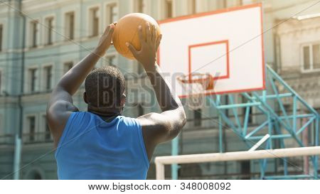 Skilled Afro-American person throwing ball into basket, active sports hobby stock photo
