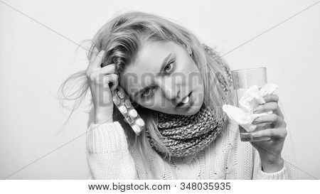 Caught a virus. Ill woman treating symptoms caused by cold or flu. Cute sick girl taking anti cold pills. Unhealthy woman holding pills and water glass. Medication and increased fluid intake stock photo