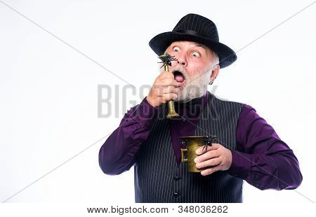 Halloween concept. Strange people. Elegant bartender wear hat and vest prepare drink. Horror themed Halloween party. Weird old grandfather with gray beard and spider. Preparing magic Halloween drink stock photo
