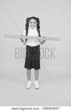 Tell me about distance. Kid school uniform hold ruler. Pupil cute girl with big ruler. Geometry school subject. Education and school concept. Sizing and measuring. School student study geometry. stock photo