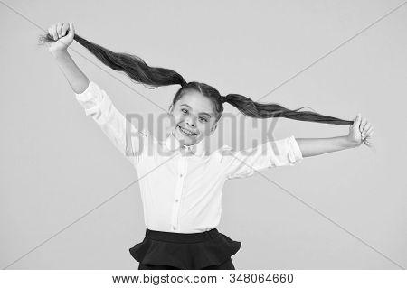 Schoolgirl pupil long hair cute ponytails hairstyle. Educational program. Adorable schoolgirl. Homeschooling or visiting regular school. Efficiency of studying. Emotional expression schoolgirl. stock photo