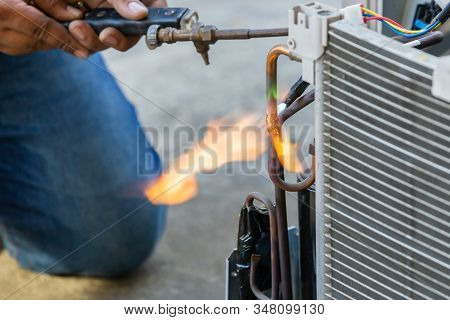 Close up of Air Conditioning Repair use fuel gases and oxygen to weld or cut metals, Oxy-fuel welding and oxy-fuel cutting processes, repairman on the floor fixing air conditioning system stock photo