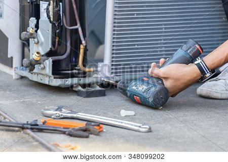 Selective focus Air Conditioning Repair, technician man hands using a screwdriver fixing modern air conditioning system stock photo