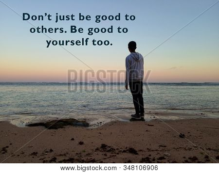 Inspirational motivational quote - Do not just be good to others. Be good to yourself too. With blurry background of young man standing alone in the calm beach looking at sunset sunrise colors view over the sea. Self love and care concept. stock photo
