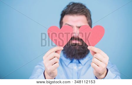 Making man feel loved. Man bearded hipster with heart valentine card. Celebrate love. Guy attractive beard and mustache in romantic mood. Feeling love. Dating and relations concept. Happy in love stock photo