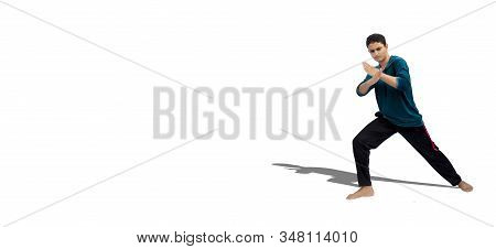 Full-length shot of aggressive alert male teenager with Asian fight style pose. Hands raised palms crossed karate style Japanese style fighting pose isolated on white background. stock photo