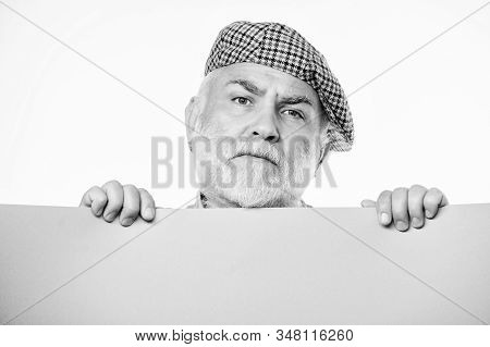 Public information. Announcement concept. Senior bearded man peek out of banner place information. Advertisement elderly people. Charming pensioner in vintage hat hold poster information copy space stock photo