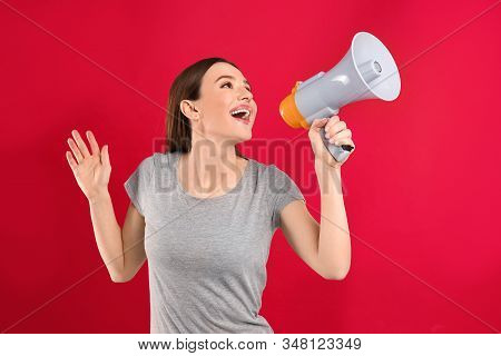 Young woman with megaphone on red background stock photo