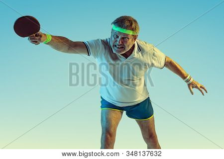 Senior man playing table tennis on gradient background in neon light. Caucasian male model in great shape stays active, sportive. Concept of sport, activity, movement, wellbeing, healthy lifestyle. stock photo