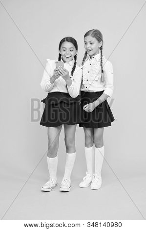 Internet is wonderful resource but access to it has hazards for kids. Girls school uniform using smartphone. Schoolgirls use mobile phone or smartphone to share photos. School application smartphone. stock photo