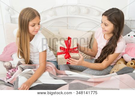 Giving tuesday. Small child giving present to sister. Little girl enjoy gift giving. Giving and receiving. Its giveaway time. Give the best. stock photo