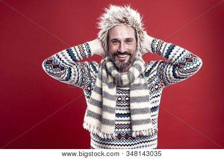 Hipster fashion winter accessories. Mature guy with beard and mustache likes to wear unusual things. Hipster is always hipster. Man bearded hipster wear furry hat striped scarf and knitted sweater. stock photo