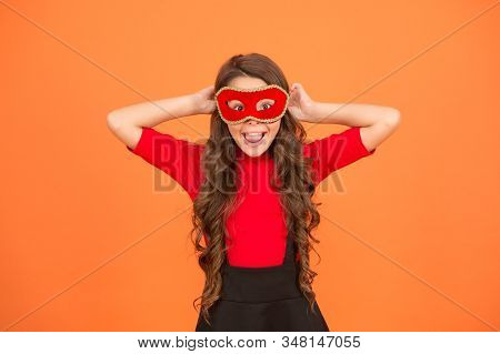 Carnival fun shop. Happy child wear venetian mask for fun. Small girl have fun with mysterious look orange background. Cool masquerade fun. Holiday celebration. Party and entertainment. stock photo
