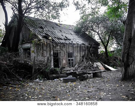 Empty old abandoned ruined house with a sharp roof surrounded by forest. The roof is decay and broken. Abandoned house in countryside. No People. stock photo