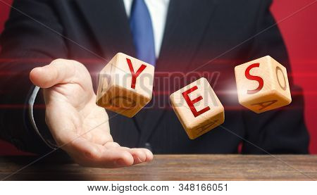 Cubes thrown by a man make up word YES. Agreement and acceptance, answer the question. Confirmation and approval. Important decision. Correct answer. Courage, irresistibility, zeal forwards, consent. stock photo