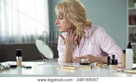 Middle-aged blond woman applying expensive makeup at home, anti-aging cosmetics stock photo