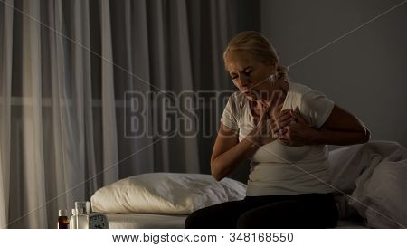 Blond elderly female touching chest, feeling sharp pain, cardiac disease infarct stock photo