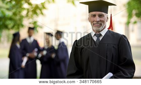 Aged man in graduation outfit, professor obtaining new degree, academic career stock photo