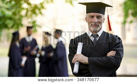 Confident man in graduation outfit, male obtaining degree, academic career stock photo