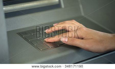 Woman entering PIN number to check bank account and withdraw money from ATM stock photo