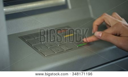 Lady entering PIN number to check bank account and withdraw money from ATM stock photo