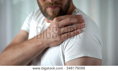 Male suffering from shoulder ache, muscle pain, inflammation sprain problem stock photo