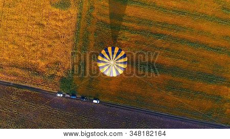 Envelope of hot air balloon landed floating in air, casting shadow over field stock photo