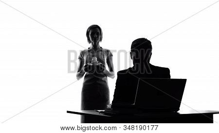 Loving woman in apron with cake looking at working husband, tasty surprise stock photo