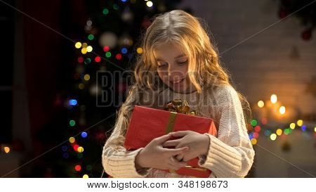 Excited blond girl holding long awaited present, magic Christmas atmosphere stock photo