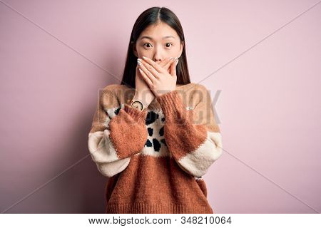 Young beautiful asian woman wearing animal print fashion sweater over pink isolated background shocked covering mouth with hands for mistake. Secret concept. stock photo