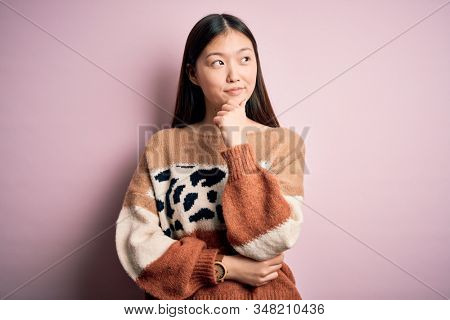 Young beautiful asian woman wearing animal print fashion sweater over pink isolated background with hand on chin thinking about question, pensive expression. Smiling with thoughtful face. Doubt stock photo