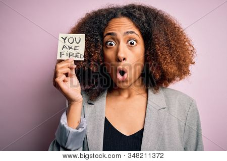 Young african american woman with afro hair holding paper with you are fired message scared in shock with a surprise face, afraid and excited with fear expression stock photo