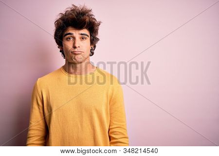 Young handsome man wearing yellow casual t-shirt standing over isolated pink background depressed and worry for distress, crying angry and afraid. Sad expression. stock photo