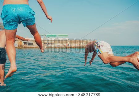 Group of happy crazy people having fun jumping in the sea water from boat. Friends jump in mid air on sunny day summer pool party at diving holiday. Travel vacation, friendship, youth holiday concept. stock photo