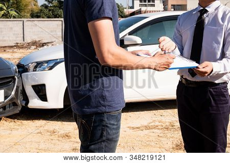The car insurance agent is checking the accident spot. Of the customer, along with the form and customer signature for car claims And process the claim. stock photo