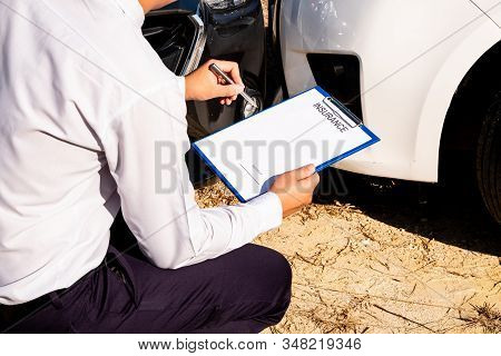 Car insurance agents are investigating the accident. Of the customer with the car claim form To assess and process accident claims. stock photo