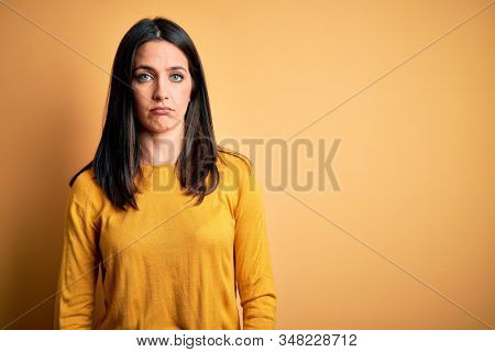 Young brunette woman with blue eyes wearing casual sweater over yellow background depressed and worry for distress, crying angry and afraid. Sad expression. stock photo