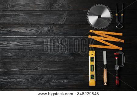 Flat lay composition with carpenter's tools on black wooden background. Space for text stock photo